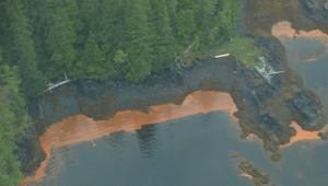 Aerial photo of Alaska coastline showing orange strip of water adjacent to land