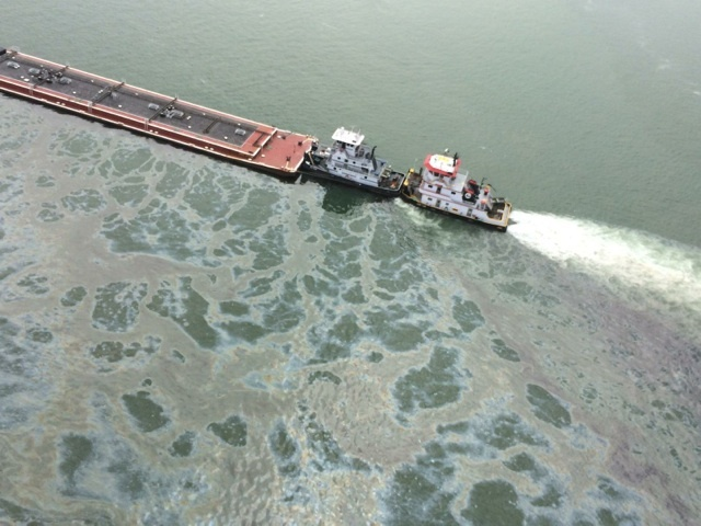 A barge loaded with marine fuel oil sits partially submerged in the Houston Ship Channel, March 22, 2014. The bulk carrier Summer Wind, reported a collision between the Summer Wind and a barge, containing 924,000 gallons of fuel oil, towed by the motor vessel Miss Susan. (U.S. Coast Guard)