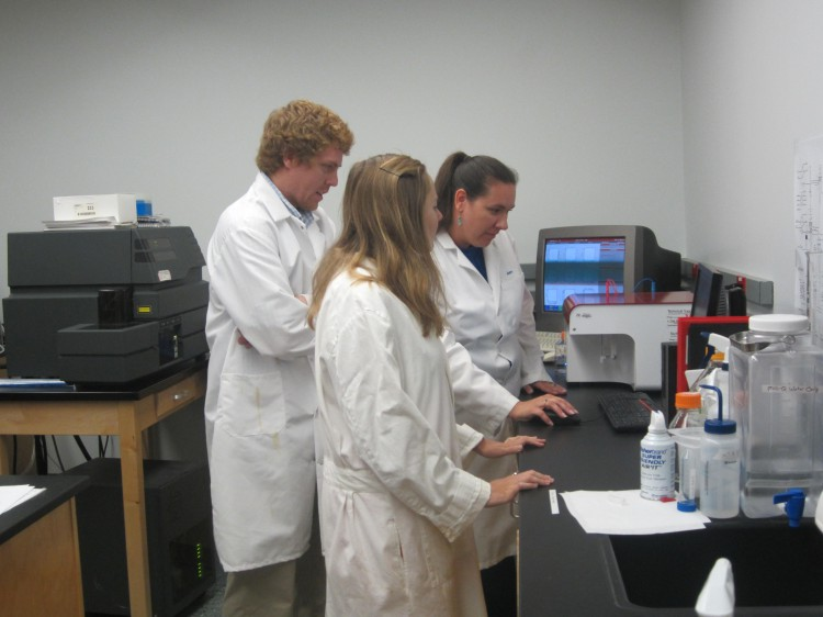 NCCOS scientists Megan Meek (front) and Jeanine Morey analyze phytoplankton samples by flow cytometry while training FWC Scientist Eric Muhlbach.  (Photo Credit: Kelly Fridey)