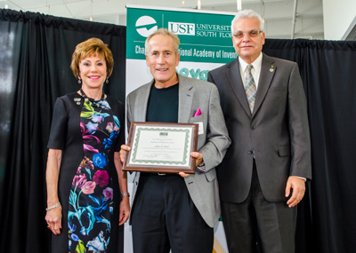NCCOS sponsored scientist Dr. John Paul (center) received a University of South Florida (USF) Excellence in Innovation Award for exceptional achievement in innovation and research at the 7th annual meeting and luncheon of the USF Chapter of the National Academy of Inventors, held August 31, 2015 at the Galleria in the USF Research Park on the university's Tampa campus. The award was presented by USF President Judy Genshaft (left) and Dr. Paul R. Sanberg (right), senior vice president for research, innovation and economic development and president of the National Academy of Inventors. Credit Christine Gitch (text) and Aimee Blodgett (photo), USF Research News