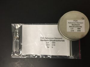 NIST Reference Material® 8642 FDA Saxitoxin Dihydrochloride Solution is provided as ten individually packaged borosilicate glass ampoules each containing approximately 1.2 mL of a 20 % ethanol/water solution containing 5 mmol/L hydrochloric acid with a reference value of 103 ± 4 µg/g Saxitoxin Dihydrochloride. With this material out of stock, a Renewal Reference Material is under preparation. Photo Credit NOAA