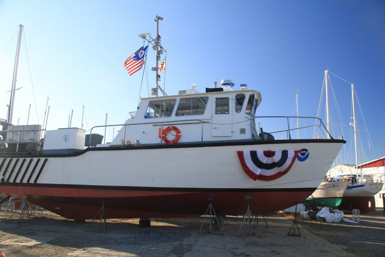R5502 is shown before the naming ceremony and dressed with American, Maryland and NOAA flags and with bunting covering her new name.