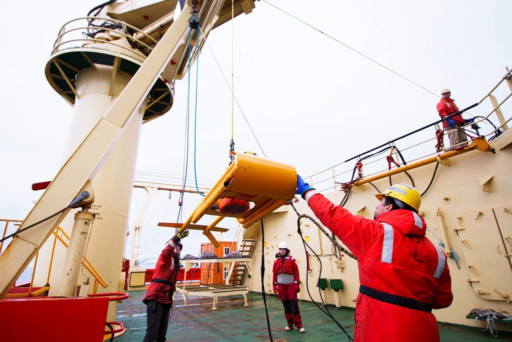 image of Dr. Chris Taylor (right) and crew prepare to deploy underwater echosounder mounted on tow fish.