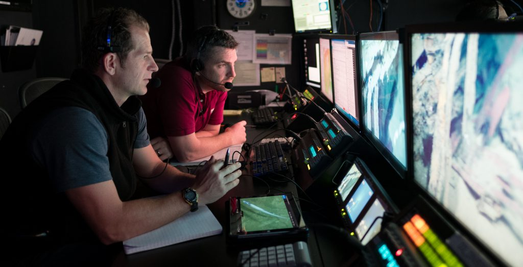 image of Dr. Daniel Wagner (left, JHT Inc./National Centers for Coastal Ocean Science) and Dr. Adam Skarke (right, Mississippi State University) in the control room of NOAA Ship Okeanos Explorer, 2018.