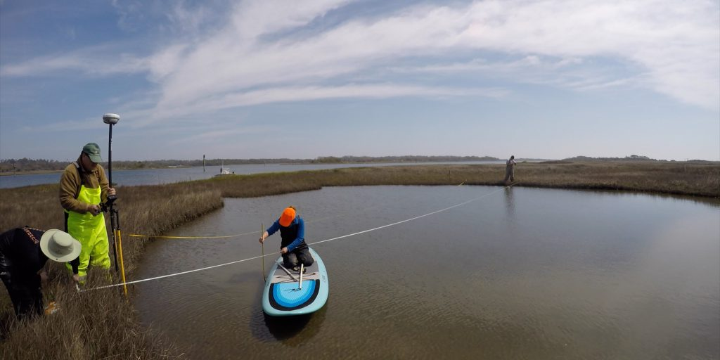 The team takes preliminary depth measurements and sediment samples of the pond that will receive dredged sediments and marsh grass.
