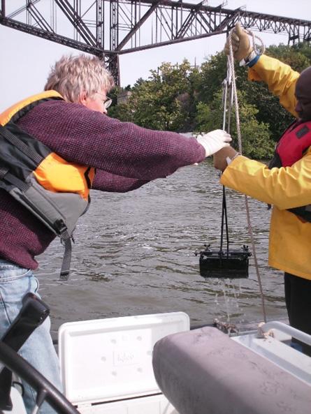 Drs. Lauenstein and Apeti retrieve a ponar sediment grab from the Hudson–Raritan estuary.