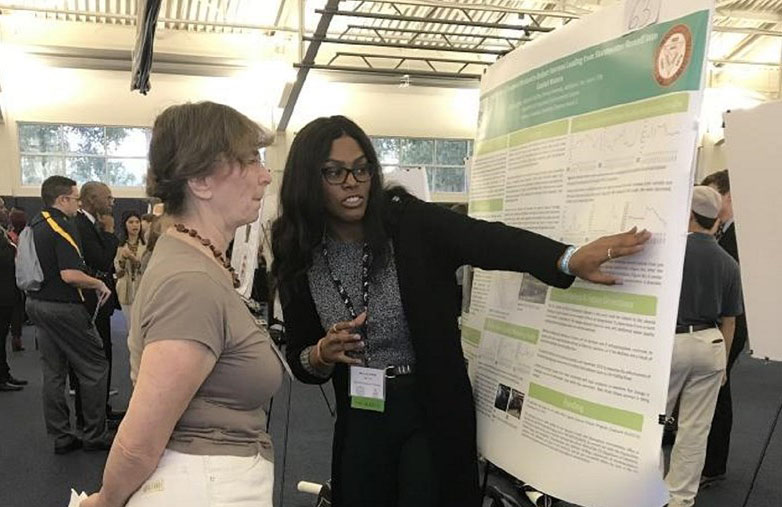 Miranda White (right) in her senior year as an undergraduate at Bethune-Cookman University explains modeling research she conducted to identify environmental indicators of harmful algal blooms in Florida's Indian River Lagoon.