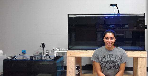 Victoria Salinas sits in front of the coral aquaculture system she is designing.Victoria Salinas sits in front of the coral aquaculture system she is designing.
