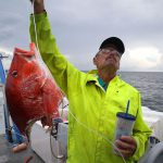 A man holds up a half-eaten red snapper as an example of depredation.