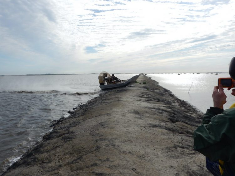 An airboat traveling over a containment berm in Sabine National Wildlife Refuge