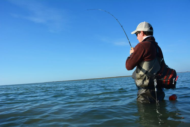 A man stands up to his thighs in the water while fishing
